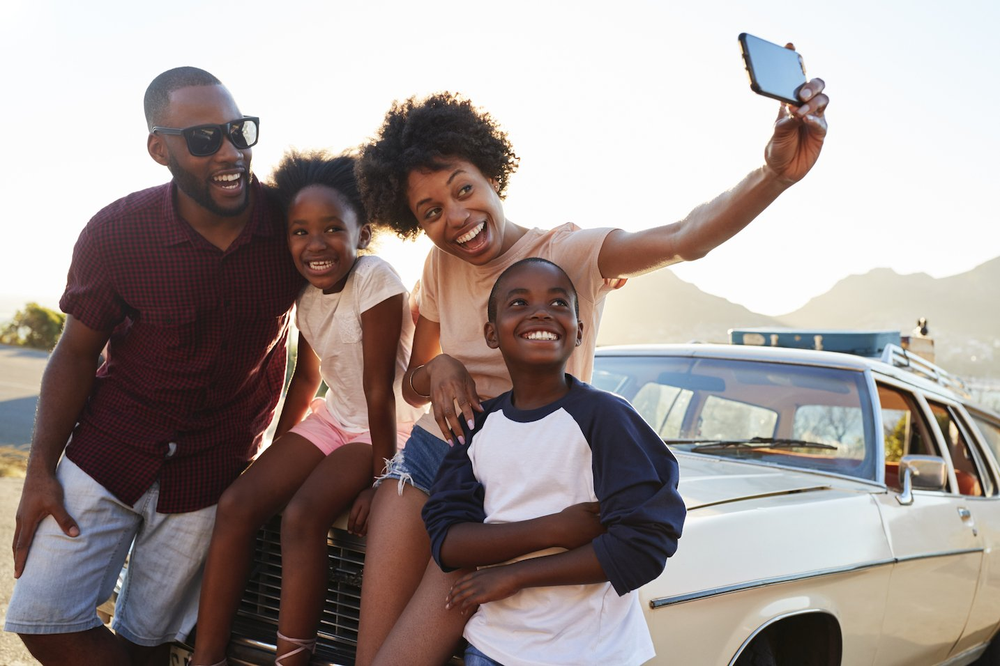 family in front of car taking selfie
