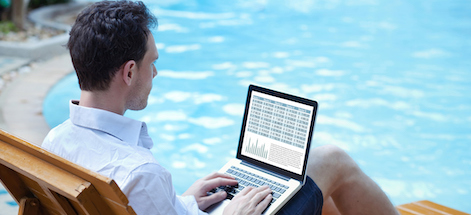 man using laptop near pool